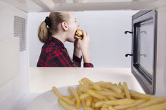 Teen girl greedily eats hamburger mouth wide open. Sitting at table near the microwave. View through open oven Stock Photography