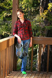 Teen Girl Grunge. A pretty trendy teenage girl standing by wooden deck railings wearing a red plaid shirt and grungy  pants with holes.  Shallow depth of field Stock Images