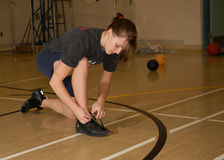Teen Girl in Gymnasium. A teen girl ties running shoe as she gets ready to play basketball in gym Stock Photography