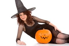 Teen girl in Halloween hat with carved pumpkin. Portrait of Latina teenager girl in black Halloween hat and fishnet dress with carved pumpkin (Jack O' Lantern Stock Photos