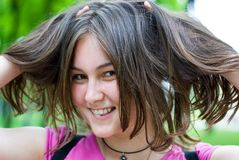 Teen girl with hands in her hair. Playfully looks into the camera Royalty Free Stock Image