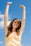 Teen Girl Happiness. Beautiful teen girl raising her arms in happiness against a vivid blue sky Royalty Free Stock Photo