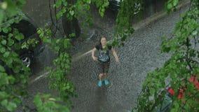 Teen girl having fun in the rain. 4K UHD. stock footage