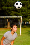 Teen girl heading soccer ball Stock Images