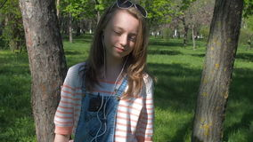 Teen girl in headphones. A girl in sunglasses and with a phone listening to music. A sunny day in the park. stock footage