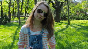 Teen girl in headphones. A girl in sunglasses and with a phone listening to music. A sunny day in the park. stock video