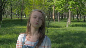Teen girl in headphones. A girl in sunglasses and with a phone listening to music. A sunny day in the park. stock video footage