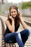 Teen girl with headphones at railways. Royalty Free Stock Photography