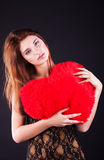 Teen girl with heart pillow. Over the black royalty free stock images
