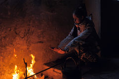 Teen girl heated by the fire in an abandoned house Royalty Free Stock Photo