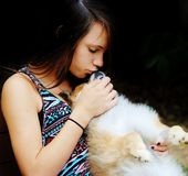 Teen girl and her dog. Teenage girl giving kisses to her pet pomeranian Royalty Free Stock Photo
