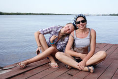 Teen Girl With Her Mother. Beauty smiling teen girl and her mother sitting on wooden moorage near river Stock Photos