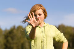 Teen girl hides her face in his hand Stock Images