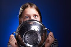 Teen girl hiding her face behind colander Stock Image