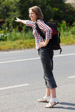 Teen girl hitch hiking Royalty Free Stock Photo