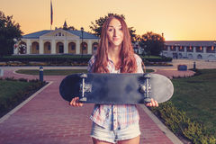Teen girl hold the skateboard befor her body Royalty Free Stock Image