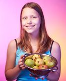 Teen girl holding a colander full of apples Stock Photo