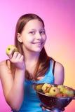 Teen girl holding a colander full of apples Stock Image