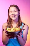 Teen girl holding a colander full of apples Royalty Free Stock Photos