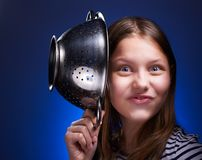 Teen girl holding colander and grimacing Royalty Free Stock Image