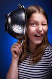 Teen girl holding colander and grimacing Royalty Free Stock Images