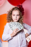 Teen girl holding a fan in her hand dollars. Stock Photos