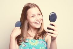 Teen girl holding hairbrush and looking at the mirror Royalty Free Stock Photography