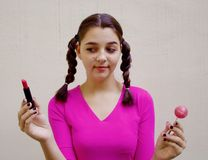 Teen girl holding lipstick and lollipop Royalty Free Stock Images