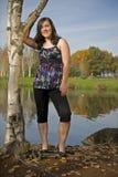 Teen girl holding onto birch tree Royalty Free Stock Photography
