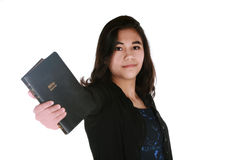 Teen girl holding out Bible. Towards viewer, serious expression Stock Images