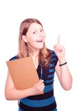Teen girl holding paintbrush and paper and gesturing Stock Image