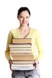 Teen girl holding pile of books. stock images