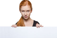 Teen girl holding a sign with copyspace for adverts. Cute teen girl holding a white sign Royalty Free Stock Photo