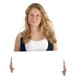 Teen girl holding white card. Blond teen girl presenting white card. Isolate taken in studio Stock Photo