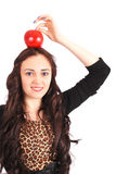 Teen girl holds an apple on her head Royalty Free Stock Image