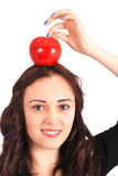 Teen girl holds an apple on her head isolated on white Stock Photo