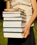 Teen girl holds a stack of books Stock Photos