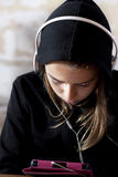 Teen girl with hoodie with tablet and headphones Royalty Free Stock Images