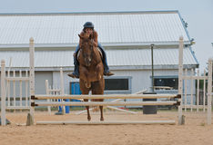 Teen girl on a horse jumping rails. Athletic teen girl jumping a horse over rails while practicing for a hunter jumper event.  Image taken from front as horse Stock Photo