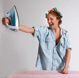 Teen girl houseworking. Girl doing housework with hair curlers. Holding an iron towards her face and standing in front of an ironing board with laughing Stock Photography