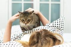 Teen girl hug cat in bed, Stock Image