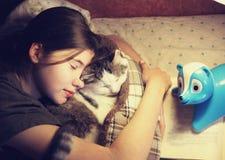 Teen girl hug cuddle cat in bed Stock Photos