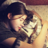 Teen girl hug cuddle cat in bed Royalty Free Stock Photo