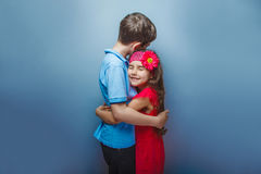Teen girl hugging a teenage  boy on gray Royalty Free Stock Image