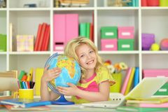 Teen girl hugging world globe. Teen girl siting at table and hugging world globe stock photo