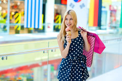 Teen girl with ice cream and shopping bags. Attractive teen blonde girl walking with ice cream and shopping bags stock photos