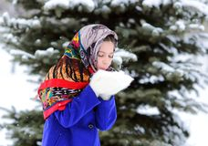 Free Teen Girl In Colored Shawl, White Mittens Blowing Snowflakes From Her Hands On Background Of Snow And Forest. Royalty Free Stock Photography - 166232237