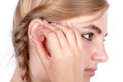 Teen girl inserting a hearing aid Stock Photo