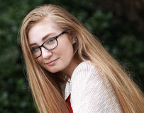 Teen girl-Instagram. Teenage girl w/ long blonde hair and black glasses wearing a red shirt and cream sweater with Instagram look royalty free stock images