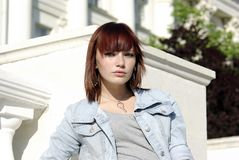 Teen girl in jacket before building [03] Royalty Free Stock Photos